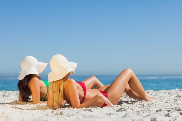 Mulheres atraentes em biquínis tomando banho de sol
