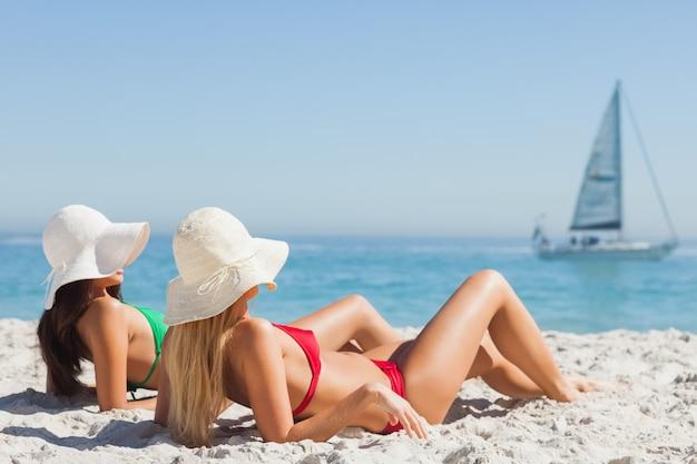Mulheres atraentes em bronzeamento de biquínis