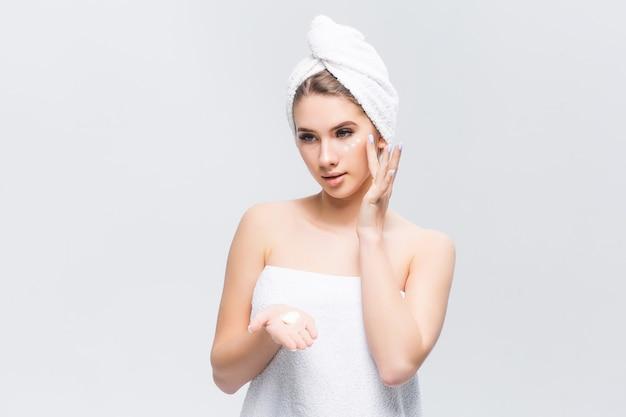 Mulheres atraentes estão aplicando creme e loção no rosto após o banho
