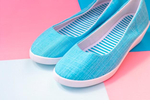 Mulheres azuis sapatos novos planos em fundo colorido
