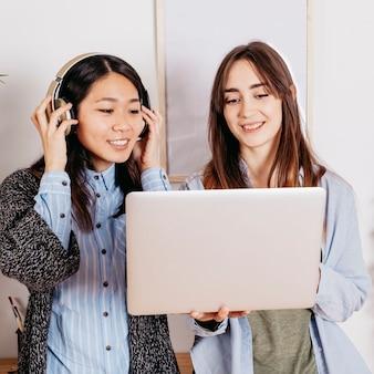 Mulheres bastante multirraciais com laptop e fones de ouvido