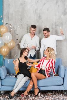 Mulheres bebendo champanhe com homens