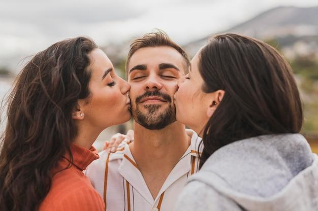 Mulheres beijando amigo masculino