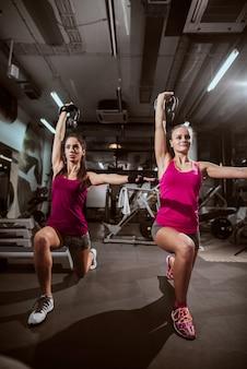 Mulheres bem formadas, fazendo exercícios com kettlebell enquanto faz lunges.
