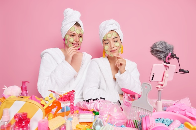 Mulheres blogueiras de beleza aplicam fatias de pepino no rosto para hidratar a pele, dão conselhos sobre como cuidar da pele vestidas com roupões de banho brancos usam diferentes produtos cosméticos