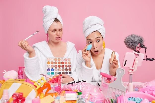 Mulheres blogueiras de beleza mostram como fazer maquiagem profissional segurar paleta de sombra para os olhos garrafa de escova cosmética de base usar roupões de banho e toalhas enroladas na cabeça gravar vídeo no smartphone