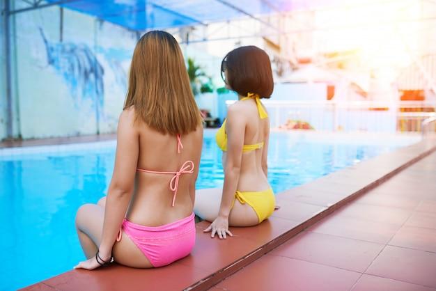 Mulheres bonitas à beira da piscina