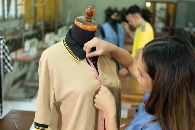 Mulheres bonitas alfaiates quando camisa de botão de gola alta com fita métrica na sala de roupas