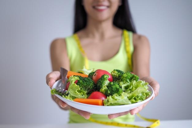 Mulheres bonitas asiáticas estão felizes em comer legumes de salada.