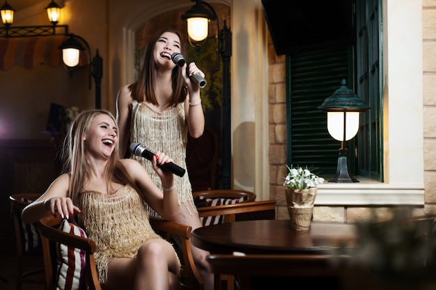 Mulheres bonitas cantando músicas de karaokê em microfones no restaurante
