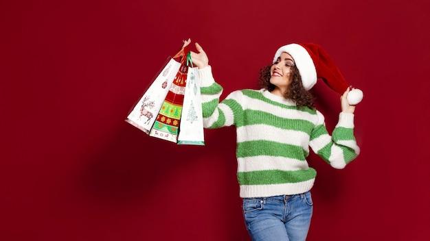 Mulheres bonitas carregando sacolas de compras coloridas de natal brilhantes sobre fundo vermelho. compras de natal e feliz ano novo.