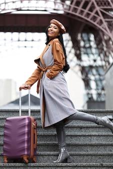 Mulheres bonitas com chapéu boina e casaco look de viagem com mala de viagem