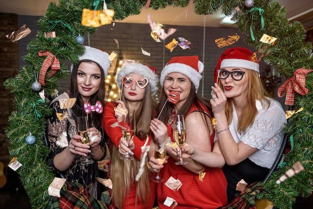 Mulheres bonitas com copos de champanhe sentadas perto da árvore de natal