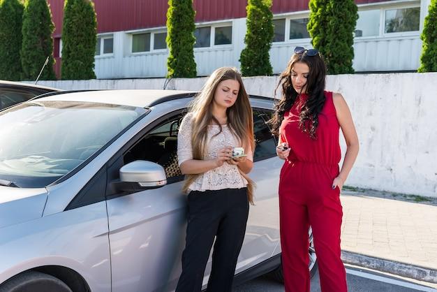 Mulheres bonitas com dólares e chaves perto do carro
