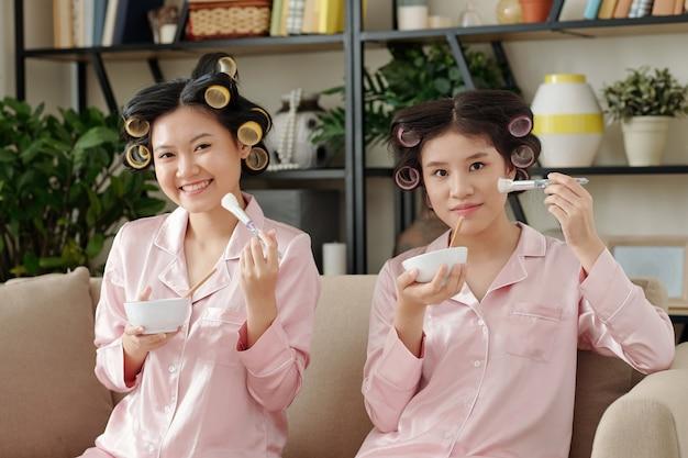 Mulheres bonitas com pijama de seda, sentadas no sofá em casa e aplicando máscara facial purificadora de poros de argila
