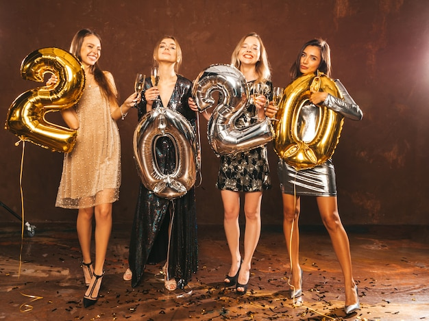 Mulheres bonitas, comemorando o ano novo. meninas lindas felizes em elegantes vestidos de festa sexy