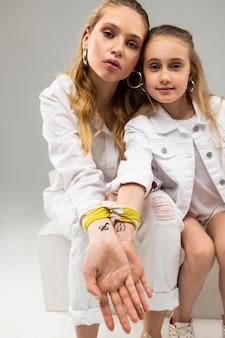 Mulheres bonitas de cabelos compridos em roupas brancas exibindo tatuagens conectadas e um pedaço de tecido amarelo