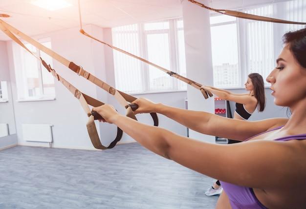 Mulheres bonitas de esportes jovens estão trabalhando com trx no ginásio