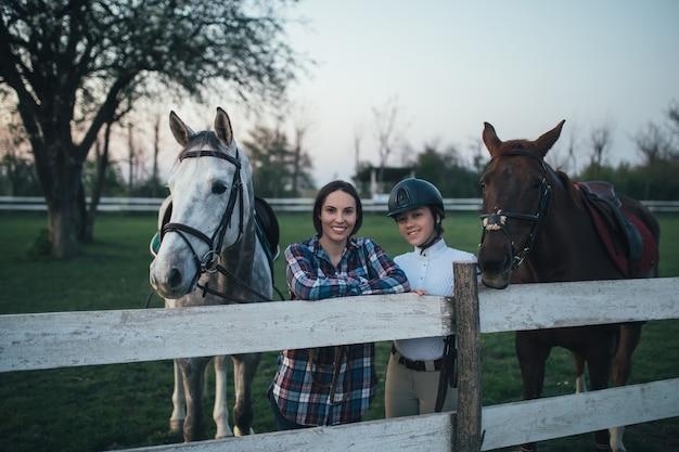 Mulheres bonitas desfrutando no rancho com seus dois cavalos.
