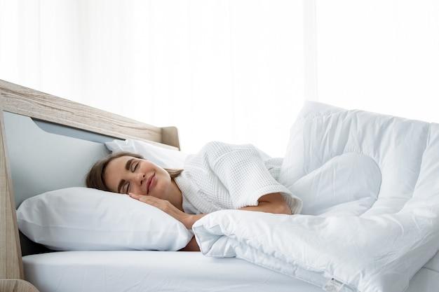 Mulheres bonitas dormem na cama em casa. conceito relaxe no quarto.