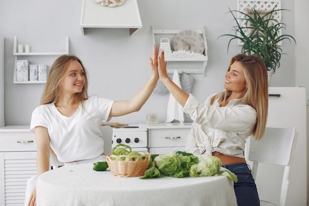 Mulheres bonitas e desportivas em uma cozinha com legumes