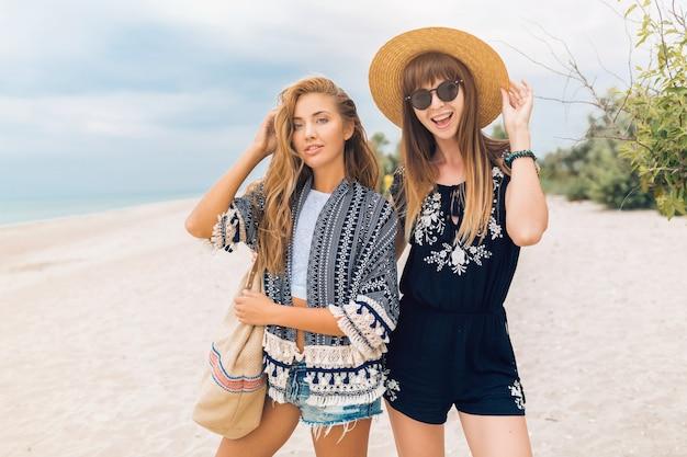 Mulheres bonitas e elegantes em férias de verão em uma praia tropical, estilo boêmio, amigos juntos, acessórios de moda, sorrindo, emoção feliz, humor positivo, shorts, chapéu de palha, se divertindo