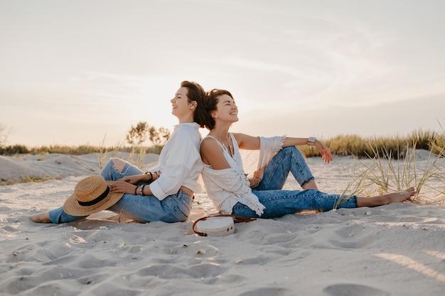 Mulheres bonitas elegantes nas férias de verão na praia, estilo boêmio, se divertindo