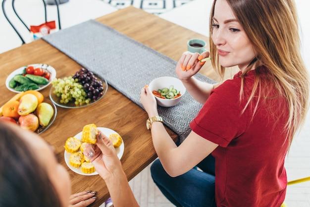 Mulheres bonitas em forma comendo salada saudável na cozinha.