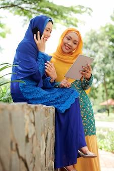 Mulheres bonitas em hijabs com dispositivos