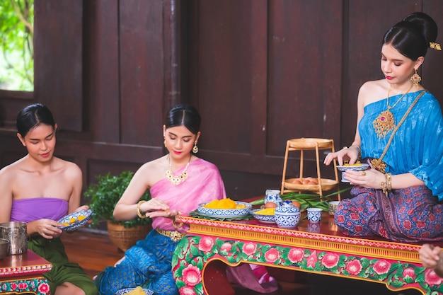 Mulheres bonitas em trajes tradicionais tailandeses estão ajudando a fazer e colocar sobremesas tailandesas em uma casa de madeira.