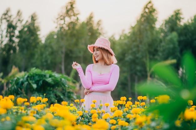 Mulheres bonitas estão de pé assistindo as flores no jardim.