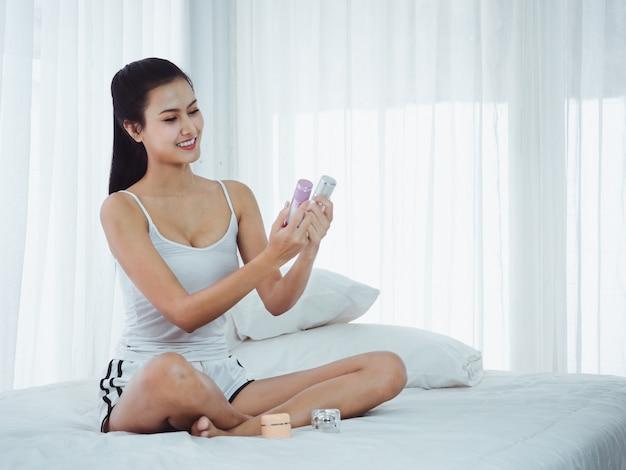 Mulheres bonitas estão escolhendo cosméticos na cama
