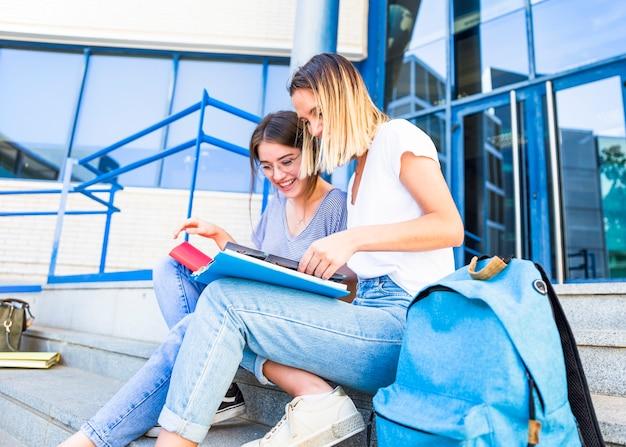 Mulheres bonitas estudando perto de prédio da universidade