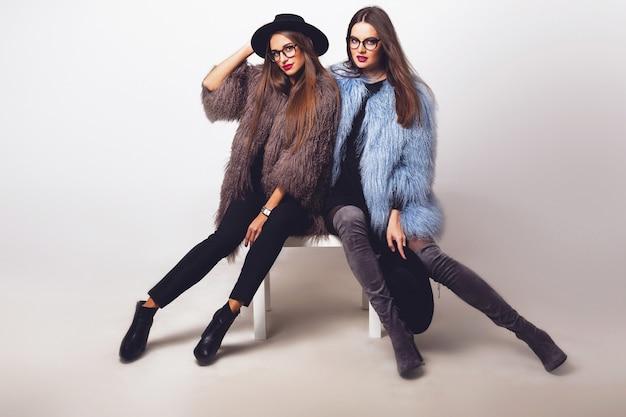 Mulheres bonitas glamourosas posando e vestindo casacos de pele