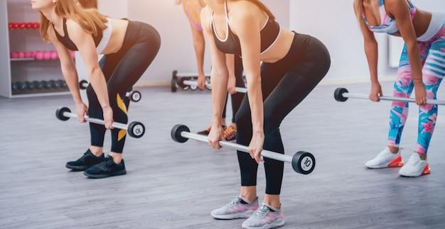 Mulheres bonitas jovens esportes bombeamento músculos com halteres no ginásio.