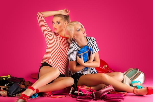 Mulheres bonitas na parede rosa. fêmeas cercadas por bolsas coloridas, bolsas e sapatos.