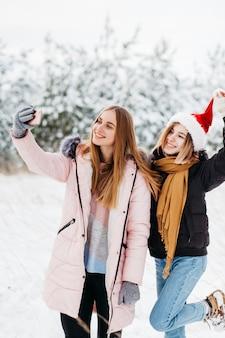 Mulheres bonitas no chapéu de papai noel tomando selfie na floresta de inverno