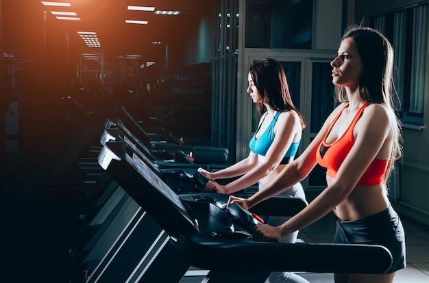 Mulheres bonitas no ginásio. correndo na esteira no clube de fitness