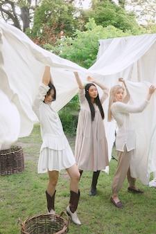 Mulheres bonitas no vestido branco que estão e que guardam o pano branco no jardim.