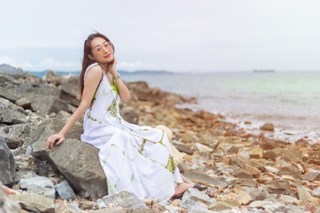 Mulheres bonitas novas no assento branco na rocha no beira-mar.