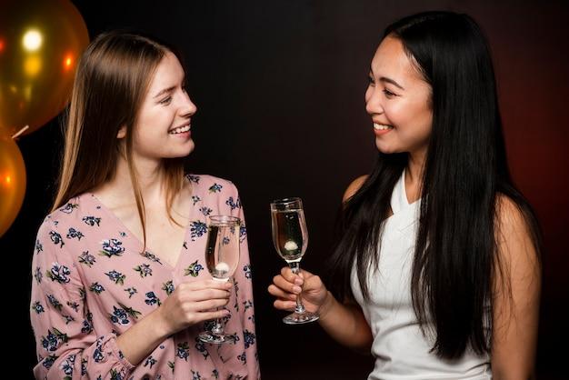 Mulheres bonitas, olhando um ao outro e segurando copos de champanhe