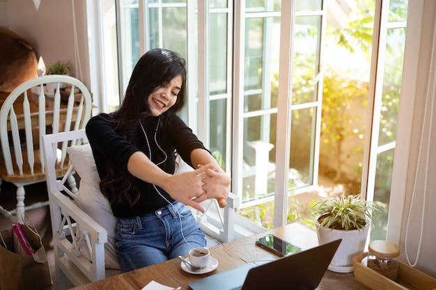 Mulheres bonitas ouvindo música e trabalhando com um laptop no café