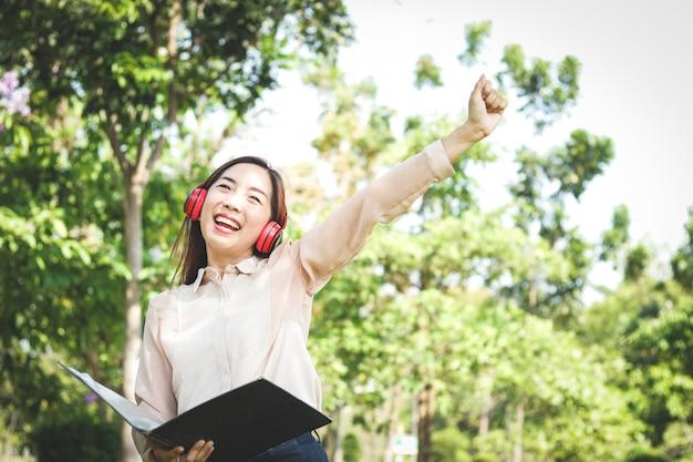 Mulheres bonitas que trabalham no escritório estão lendo dados em arquivos de documentos enquanto usavam fones de ouvido