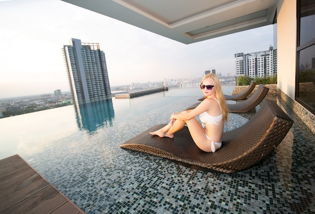 Mulheres bonitas relaxantes no spa resort à beira da piscina de luxo.