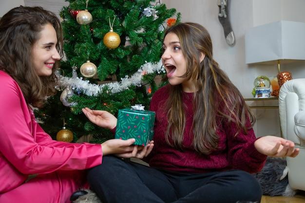 Mulheres bonitas sentadas perto da árvore de natal em casa trocando com presentes se divertindo