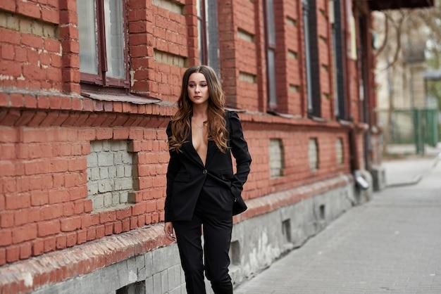 Mulheres bonitas sexy. garota fashion em um terno preto perto da parede de tijolo. streetwear das mulheres 2020. mulher de estilo de rua. como se vestir nesta primavera de 2020