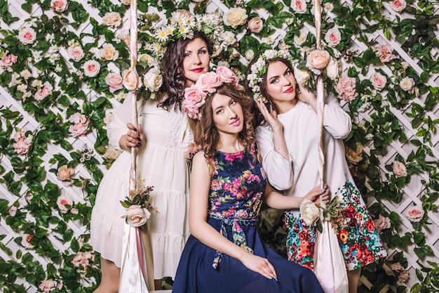Mulheres bonitas sorrindo alegremente balançando em um balanço entre as flores em grinaldas