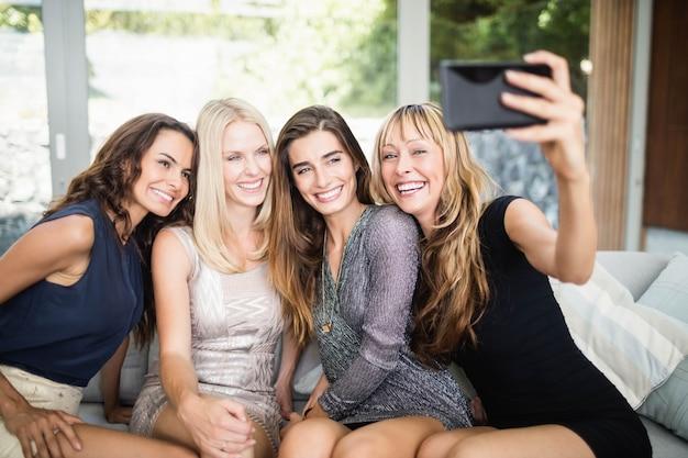 Mulheres bonitas, sorrindo e tomando selfie com telefone móvel na festa