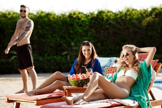 Mulheres bonitas sorrindo, fazendo selfie, relaxando perto da piscina