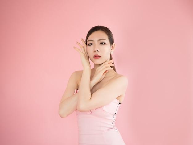 Mulheres bonitas, tocar, dela, bochecha, e, rosto, com, mãos, menina asiática, posar, em, estúdio